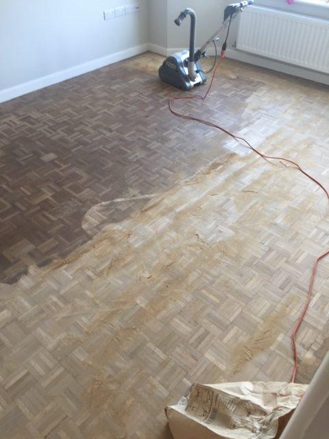 Sanding wooden parquet flooring